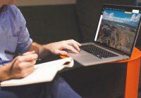 Homme travaillant sur son ordinateur avec son cahier
